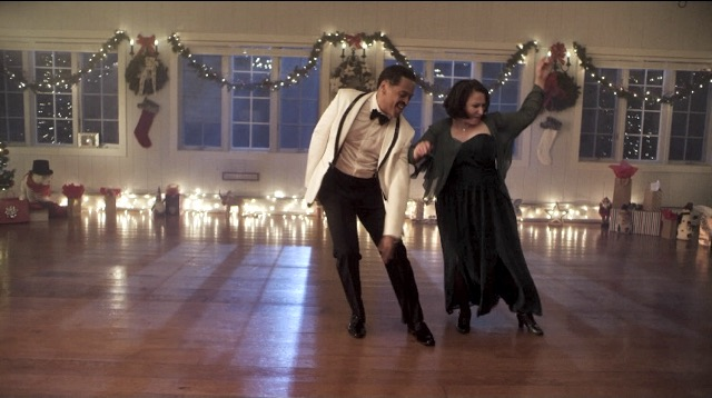 a man and woman tap dance in a large room with bare floor and Christmas decorations