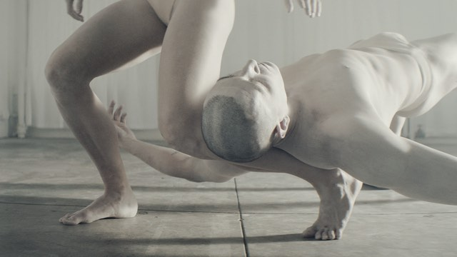 two white-paint-covered dancers, one resting his head on the other's ankle