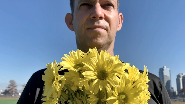 a light skinned man in a tee shirt holds yellow flowers