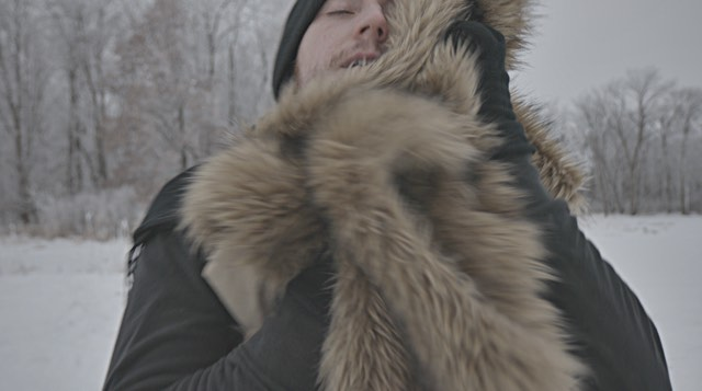 a light skinned man rubs his face in a furry coat
