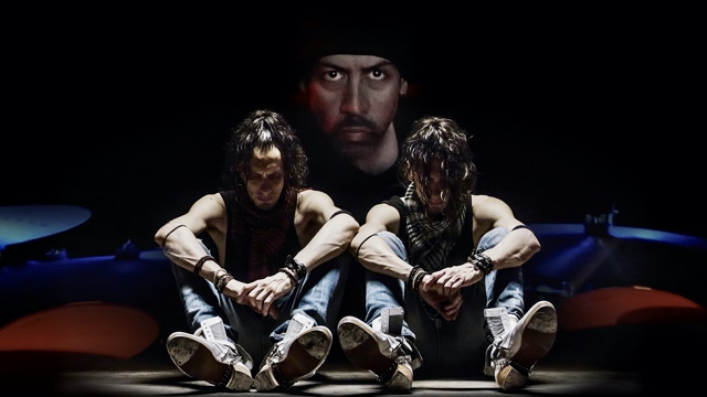 twin dancers in tap boots and jeans sit side by side, with another man's face projected behind