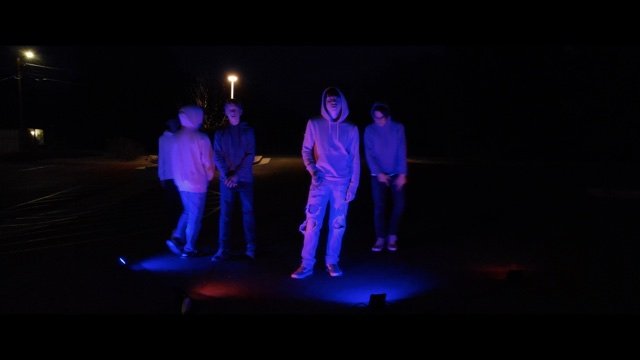 four people in hoodies and jeans at night