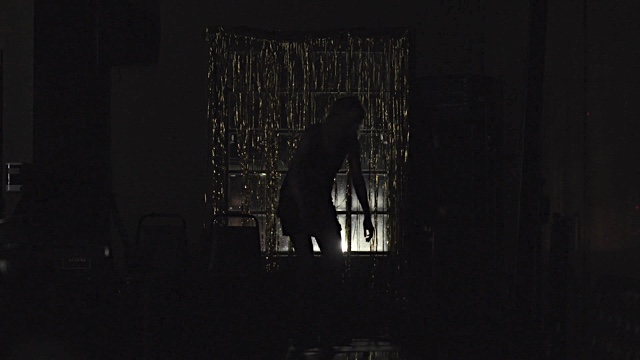 the silhouette of a dancer against a window in a dark room
