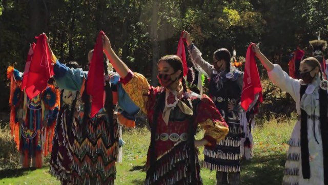 several Native American dancers raise a hand holding a red flag