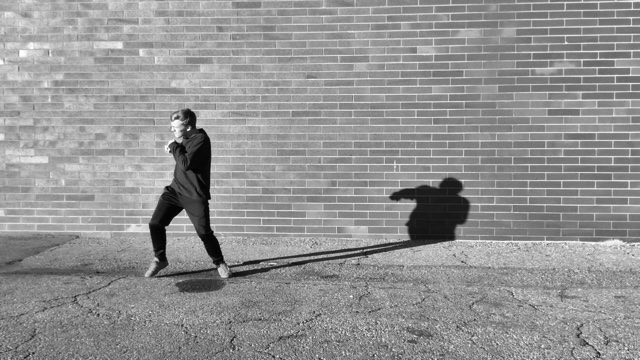 a young male dancer steps toward the sun, his shadow long behind him