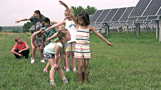 many young dancers in a line making eye contact, alongside a solar panel array