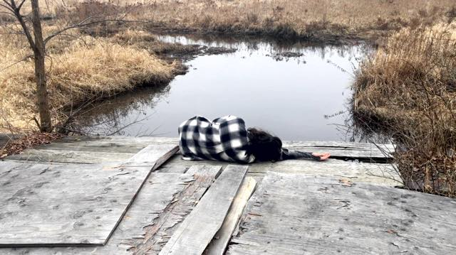 a dark haired person lays on their side atop old plywood next to a pond