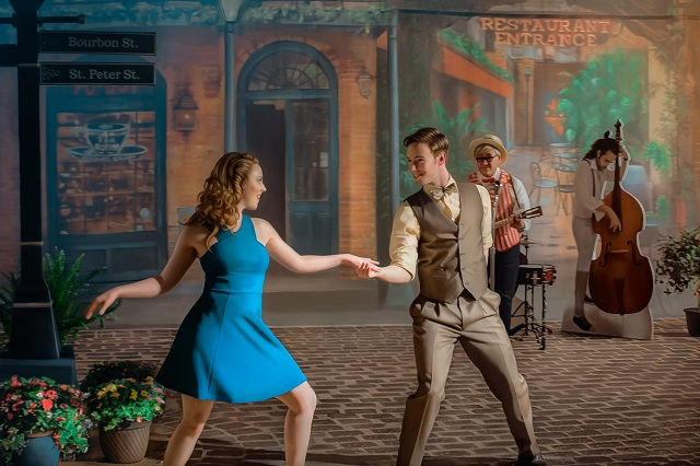 a young man and young woman dance on a brick street while musicians play in the background