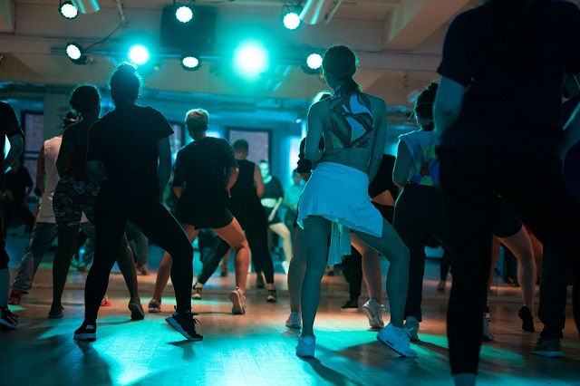 several people face the instructor of a jazz dance class